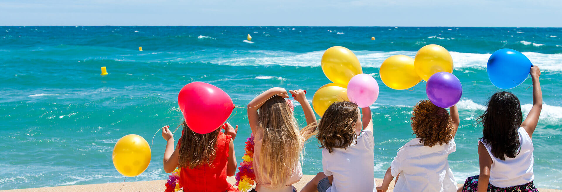 Kids on beach with balloons